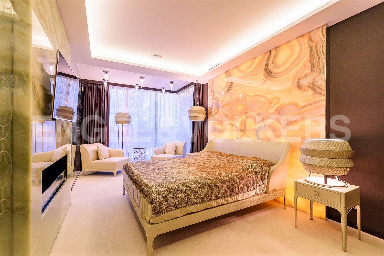 Мастер-спальня с камином и теплой подсветкой натурального камня